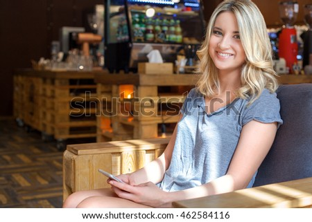 Young cute blonde girl smiling on camera and holding her smart phone in hands while sitting in modern coffee shop during lunch break.