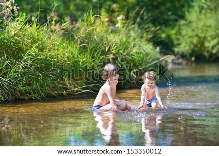 Young cute boy and his little baby sister playing in the water in a beautiful river on a sunny summer day - stock photo