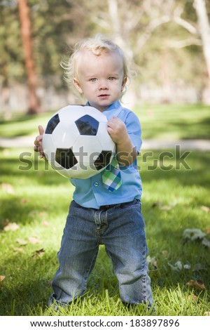 Young Cute Boy Playing with Soccer Ball in the Park.