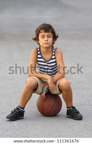 Young cute boy with basketball ball - stock photo