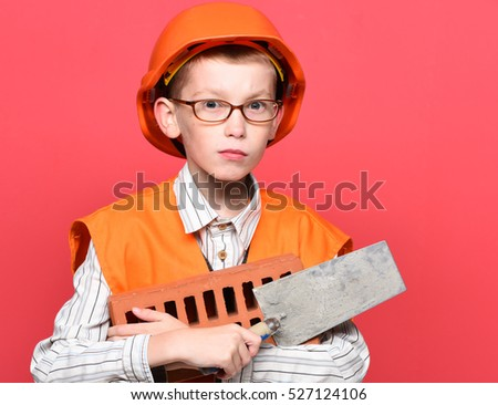 young cute builder boy in orange uniform and hard hat or helmet with glasses holding tool or putty knife and brick on red studio background