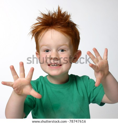 Young cute cheeky boy with spikey red hair, holding hands up with five fingers wearing green t shirt