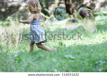 young cute child girl blowing big soap bubbles - stock photo