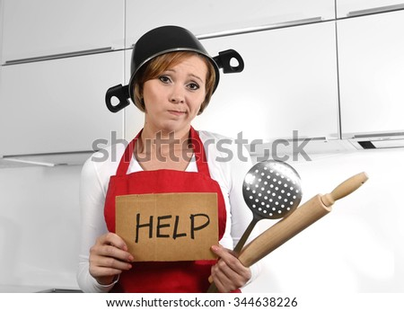 young cute cook woman confused and frustrated face expression wearing red apron asking for help holding rolling pin and cooking pot on the head at home kitchen in domestic stress and lifestyle concept - stock photo