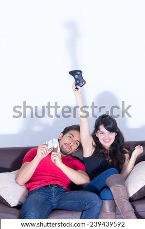 young cute couple playing video games having fun in livingroom - stock photo