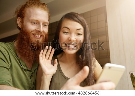 Young cute couple recording video for congratulating their friend on his birthday. Pretty student girl saying hello while taking selfie together with her redhead boyfriend using electronic device