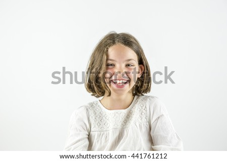Young cute giggly girl smiling in to the camera isolated on white background.