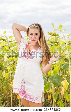 Young cute girl posing in sunflower field