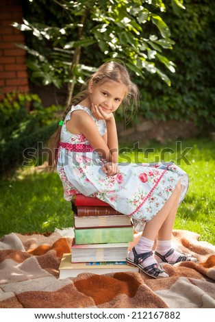 Young cute girl sitting on big stack of books at garden