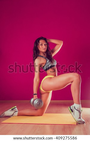 Young cute girl tanned brunette goes in for sports in a beautiful dress on a pink background