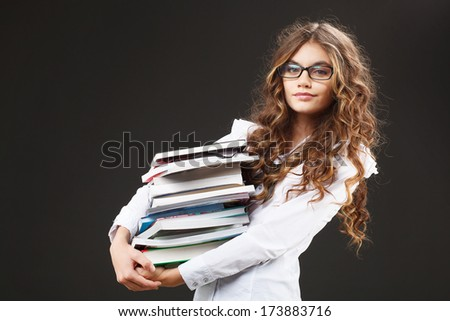 Young cute girl with stack of books - stock photo
