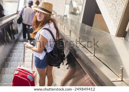 Young cute girl with the red suitcase standing on the escalator. Travel concept. - stock photo