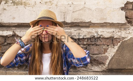 Young cute hipster girl standing in the street old town and closes his eyes his hands with colored nails. - stock photo