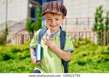 Young cute kid with book in front of school building. - stock photo