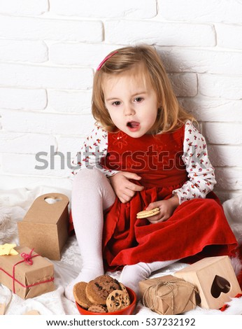 young cute little blonde girl in christmas red dress sitting around xmas gifts or presents and eating cookie on white brick wall background