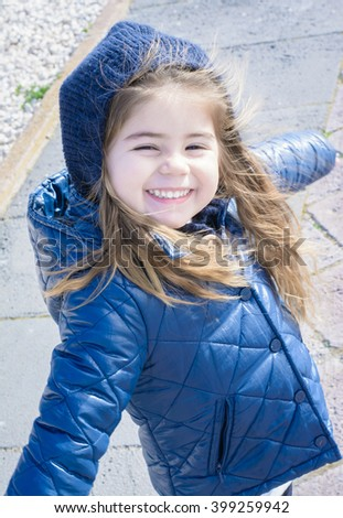 Young cute little girl smiling in an winter outdoor day - stock photo