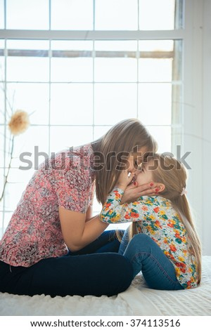 Young cute mother having good time playing with her beautiful daughter in the bed in a big bright room on a sunny day - stock photo