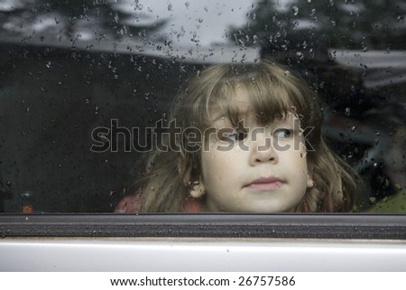young cute pensive girl looking through window of car. Window covers of rain`s drops - stock photo