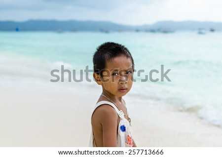 Young cute poor Asian boy in a ragged t-shirt from impoverished area with deep thoughtful sight against turquoise sea at white beach on Boracay island, Philippines - stock photo