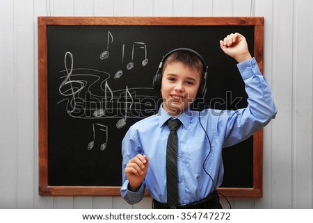 Young cute schoolboy wearing headphones at the blackboard with musical notes - stock photo