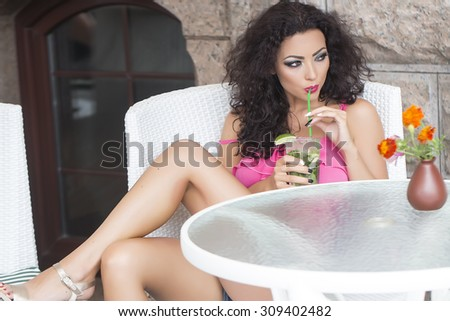 Young cute sexy brunette lady with curly hair sitting in white chair in cafe at table with vase of fresh orange marigold flowers drinking alcoholic mojito cocktail with straw, horizontal picture - stock photo