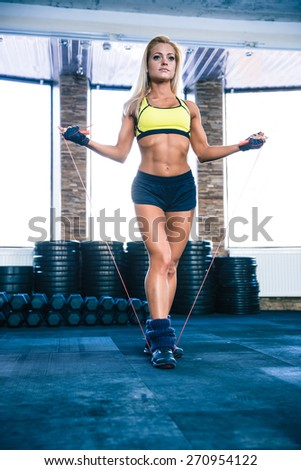 Young cute sporty woman workout with jumping rope in crossfit gym - stock photo