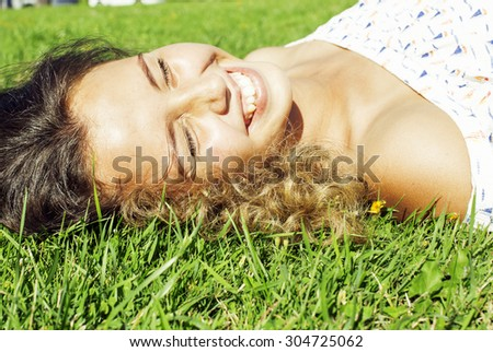 young cute summer girl on green grass outside relaxing smiling close up - stock photo