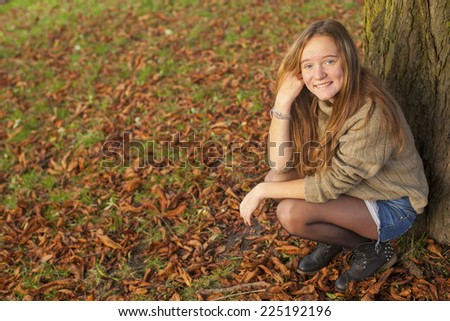 Young cute teen girl in autumn park. - stock photo