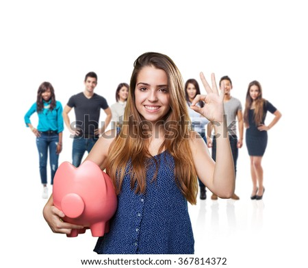 young cute woman doing okay gesture holding a piggy bank - stock photo
