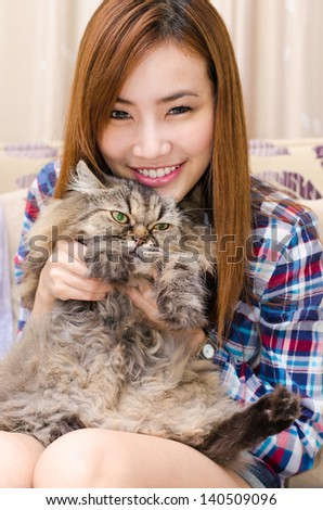 Young cute woman holding her pet cat. - stock photo