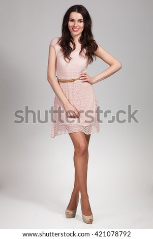 Young cute woman posing in beige dress - stock photo