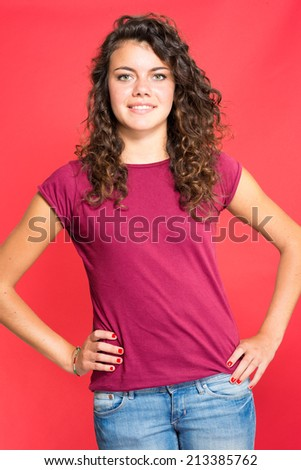 Young cute woman posing on red background