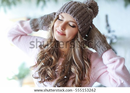Young cute woman with long hair in a hat and gloves in the winter