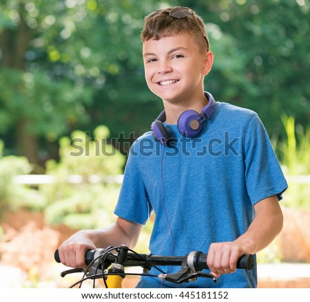 Young cyclist on a bike in the park. Teen boy 12-14 year old with bike posing outdoors. - stock photo