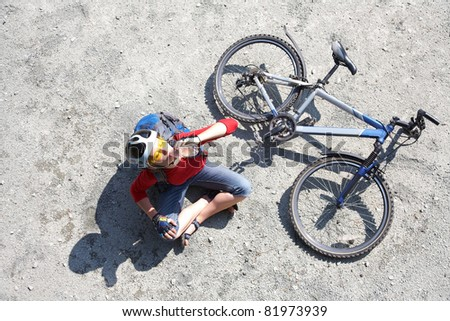 Young cyclist on a mountain bike drinks water - stock photo