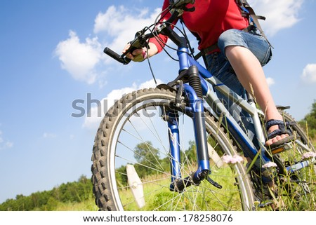 Young cyclist on a mountain bike in green park - stock photo