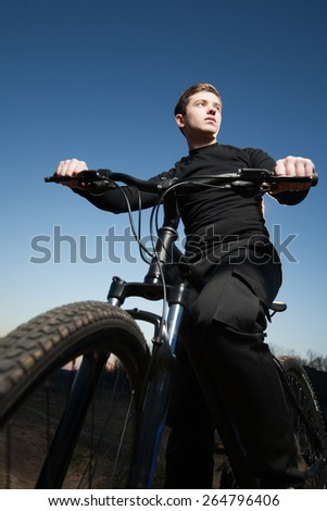 Young cyclist on bike riding a field,  trail at sunrise. - stock photo
