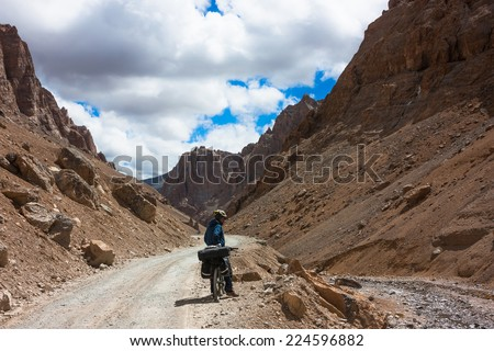 Young cyclist standing on mountains road. Himalayas, Jammu and Kashmir State, North India