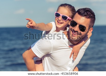Young dad and his little daughter in sun glasses are looking away and smiling. Girl is sitting on her father's shoulders and pointing, sunny sea in the background - stock photo