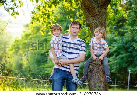Young dad and his two little sons, kid boys standing near  tree. Happy family of three, having fun  on warm sunny day. Active leisure with kids - stock photo