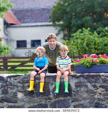 Young dad and two little kid boys sitting together on stone bridge in european village. Happy family of three. Twins in colorful gumboots, outdoors.