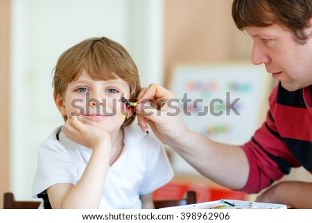 Young dad painting flag on face of little son for football or soccer game. Kid boy fan happy about game of team in champions league. Selective focus - stock photo