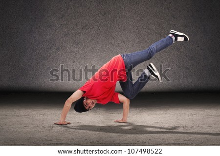 Young dancer doing a breakdance style in front of grey background - stock photo