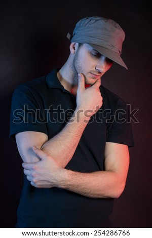 young dancer isolated on black background in studio. Young man standing and holding chin - stock photo