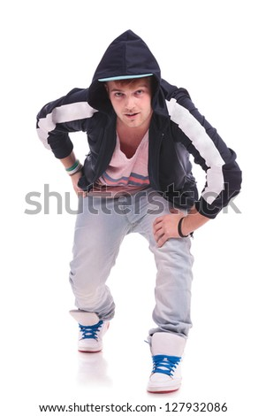 young dancer man leaning forward on his knee, looking at the camera