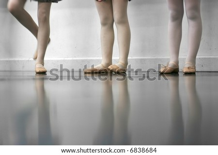 Young dancers are learning - they're witing to see what the instructor says to do next... low angle shot of just their feet and legs - this view has had the color removed from the floor and wall. - stock photo