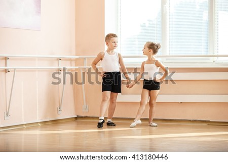 Young dancers doing an exercise while warming up at ballet class