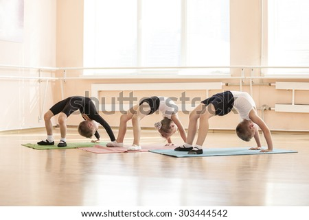Young dancers performing bridge exercise while warming up at ballet class - stock photo