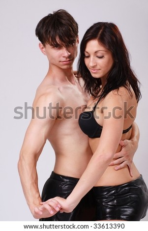 Young dancing couple on a gray background