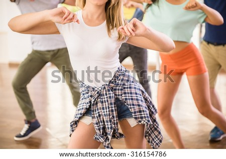 Young dancing people in gym during exercise dancer workout training with happy fresh energy. - stock photo
